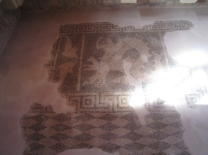 Late 4th/early 3rd century B.C. This pebble mosaic floor belongs to an earlier Hellenistic building and depicts Scylla, the mythical sea-monster who is part -woman, part-fish and part-dog. She is illustrated holding a ship mast and a trident and is surrounded by illustrations of sea life.